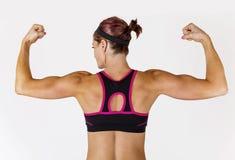 Den starka härliga konditionkvinnan som böjer hennes arm, tränga sig in Fotografering för Bildbyråer
