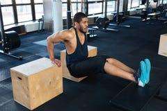 Den starka konditionmannen pumpar biceps genom att använda utbildningsapparaturen Arkivfoton