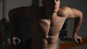 Den starka kraftiga mannen övar för bröst- muskler och triceps med dopp Närbild lättnad av kroppen stock video