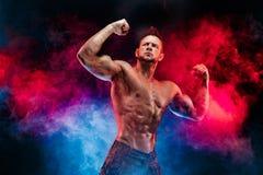 Den starka kroppsbyggaremannen i militär flåsar med perfekt abs, skuldror, biceps, triceps, bröstkorg Royaltyfri Fotografi