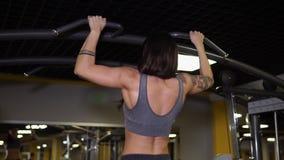 Den starka kvinnan gör pullups i idrottshall lager videofilmer