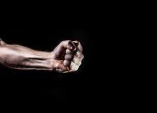 Den starka manliga mannen lyftte näven på en svart bakgrund, makt, krig, p royaltyfria foton