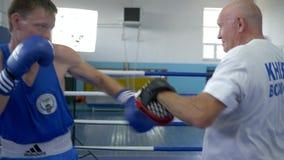 Den starka muskelmannen utför boxareslag med instruktören på cirkeln för konkurrens på komplexa sportar stock video