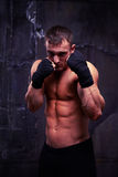 Den starka muskulösa boxaren är klar att slåss att posera över svart backgr Fotografering för Bildbyråer