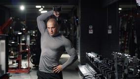 Den starka muskulösa mannen som gör sportövningar med hantlar, utbildar tricepens, muskler av händer i den mörka idrottshallen A arkivfilmer