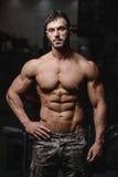 Den starka och stiliga idrotts- unga mannen tränga sig in abs och biceps Royaltyfria Foton