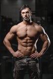 Den starka och stiliga idrotts- unga mannen tränga sig in abs och biceps royaltyfri fotografi