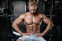 Den starka och stiliga idrotts- unga mannen tränga sig in abs och biceps Arkivbilder