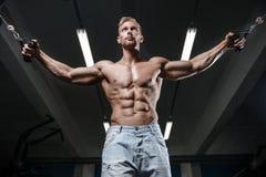 Den starka och stiliga idrotts- unga mannen tränga sig in abs och biceps arkivfoto