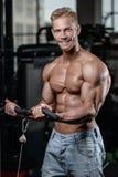 Den starka och stiliga idrotts- unga mannen tränga sig in abs och biceps Arkivfoton