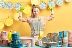 Den starka rynka pannan kvinnan med lyftta armar är klar att tvätta disken efter parti royaltyfri bild