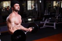 Den starka sunda vuxna människan rev sönder mannen med stora muskler som utbildar med b royaltyfri fotografi