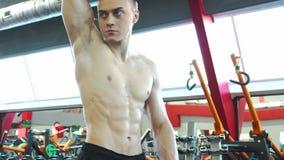 Den starka unga manliga kroppsbyggaren ser hans reflexion i spegeln lager videofilmer