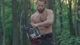 Den starka woodcuteren som sågar trädet med chainsawen långsamt arkivfilmer