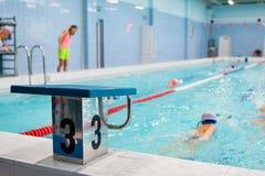 Den startande plattformen med nummer tre är i simbassängen för fyra gränder för barngrupper Ungar gör övningar med en instruktör Fotografering för Bildbyråer