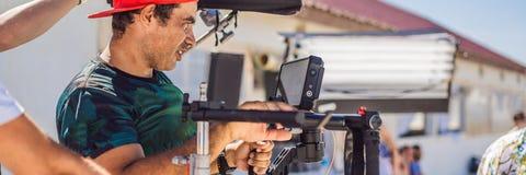 Den Steadicam operatören förbereder kameran och stabilisator-gimbalen för 3 axel för ett kommersiellt forsBANER, LÅNGT FORMAT arkivfoton