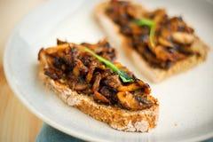 Den stekte champignonen med vitlök på rostat hemlagat bröd för helgfrukost på den prickiga plattan och med vit snör åt bandet royaltyfri foto