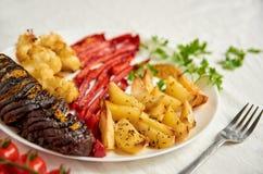Den stekte potatisar, aubergine, spansk peppar och blomkålen på det vita plattaslutet dekorerade upp med gaffeln, körsbärsröda to Royaltyfri Foto