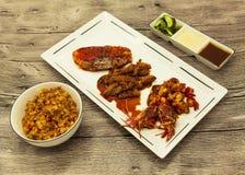 Den stekte tigerräkor och bläckfisken i en kinesisk stil grillade grillfesten i en kryddig olja med stekte ris och såser Royaltyfri Foto