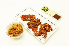 Den stekte tigerräkor och bläckfisken i en kinesisk stil grillade grillfesten i en kryddig olja med stekte ris och såser Arkivfoton
