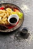 Den stekte tioarmade bläckfisken ringer med grönsaker och soya på den svarta plattan Arkivbilder