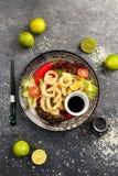 Den stekte tioarmade bläckfisken ringer med grönsaker och soya på den svarta plattan Royaltyfri Bild
