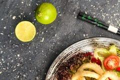 Den stekte tioarmade bläckfisken ringer med grönsaker och soya på den svarta plattan Royaltyfria Bilder
