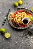 Den stekte tioarmade bläckfisken ringer med grönsaker och soya på den svarta plattan Royaltyfria Foton
