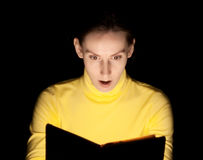 Ung kvinnaläsning bokar förvånadt undra Arkivbild