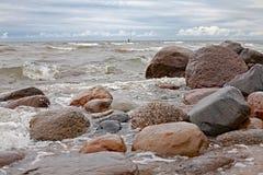 Den steniga havskusten i blåsväder, med den ensamma surfaren på ett avståndsskott royaltyfria foton