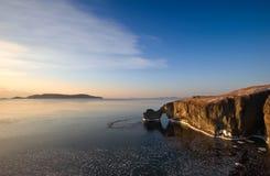 Den steniga kusten av den kalla vintermorgonen Arkivbild