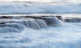 Den steniga kusten med det krabba havet och vågor som kraschar på, vaggar Royaltyfria Bilder