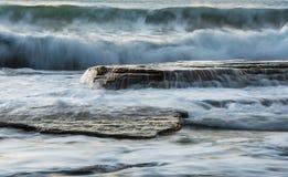 Den steniga kusten med det krabba havet och vågor som kraschar på, vaggar Arkivfoto