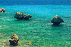 Den steniga kusten som förbiser turkosblåtthavet i varm summe Royaltyfri Fotografi