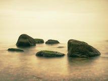 Den steniga kusten trotsar till havfrikändhimmel med den suddiga solen i hög fuktighet fotografering för bildbyråer