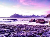 Den steniga stranden och klippan av den steniga fjärden Blåttsignaler av den Februari solnedgången, rosa horisont Arkivbild
