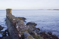 Den steniga strandremsan och stenen byggde kopiabefästningar på sjösidabyn av Groomsport i räkning ner i nordliga Irel Arkivbilder