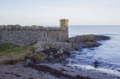 Den steniga strandremsan och stenen byggde kopiabefästningar på sjösidabyn av Groomsport i räkning ner i nordliga Irel Arkivbild