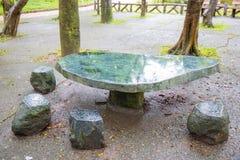 Den stentabellen och bänken i trädgården arkivfoton