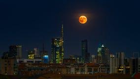 Den stigande fullmånen i Milan vid natt arkivfoton
