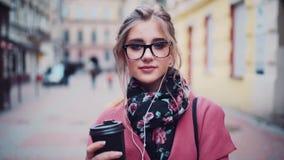 Den stilfulla affärskvinnan i en varm härlig halsduk som rymmer, kaffe-till-går och ser charmingly in mot kameran innegrej stock video