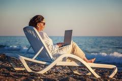 Den stilfulla attraktiva mogna kvinnan 50-60 gör bruk av bärbara datorn på Arkivfoto