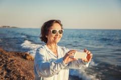 Den stilfulla attraktiva mogna kvinnan 50-60 gör foto av mobil pho Royaltyfri Fotografi