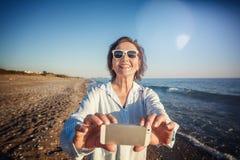 Den stilfulla attraktiva mogna kvinnan 50-60 gör foto av mobil pho Arkivfoto