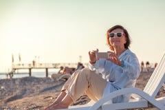 Den stilfulla attraktiva mogna kvinnan 50-60 gör foto av mobil pho Royaltyfri Bild