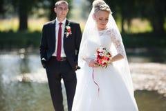 Den stilfulla blonda caucasian lyckliga bruden med brudgummen poserar på th fotografering för bildbyråer