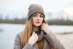 Den stilfulla blonda kvinnan i moderiktigt stads- outwear att posera kallt väder på flodbanken Genomdränkt färg för tappningfilte arkivbilder