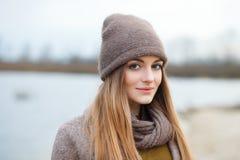 Den stilfulla blonda kvinnan i moderiktigt stads- outwear att posera kallt väder på flodbanken Genomdränkt färg för tappningfilte royaltyfria foton