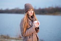 Den stilfulla blonda kvinnan i moderiktigt stads- outwear att posera kallt väder på flodbanken Genomdränkt färg för tappningfilte royaltyfri fotografi