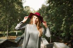 Den stilfulla blonda modellen som poserar på parkera i moderiktigt, värme klänningen och Royaltyfri Foto